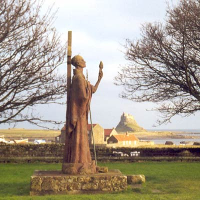 Statue in country side, castle overlooking in background.