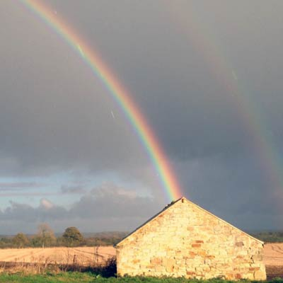 Stone barn house with rainbow and countryside in background.